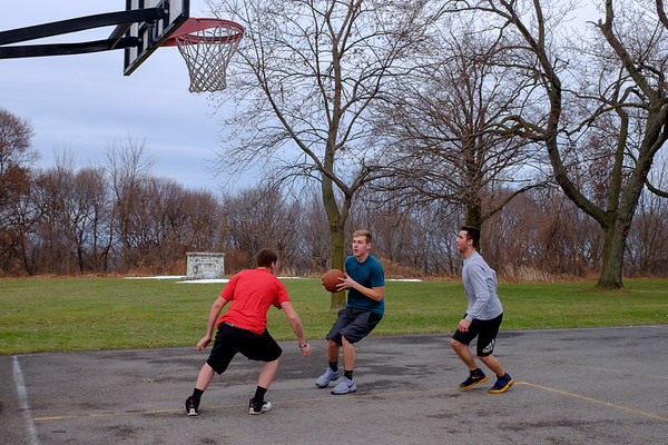 JOED VIERA/STAFF PHOTOGRAPHER-Lockport, NY-Chris Moss, Maddox Mcgary and Tod Main play a pickup game of basketball at Outwater Park Thursday afternoon.