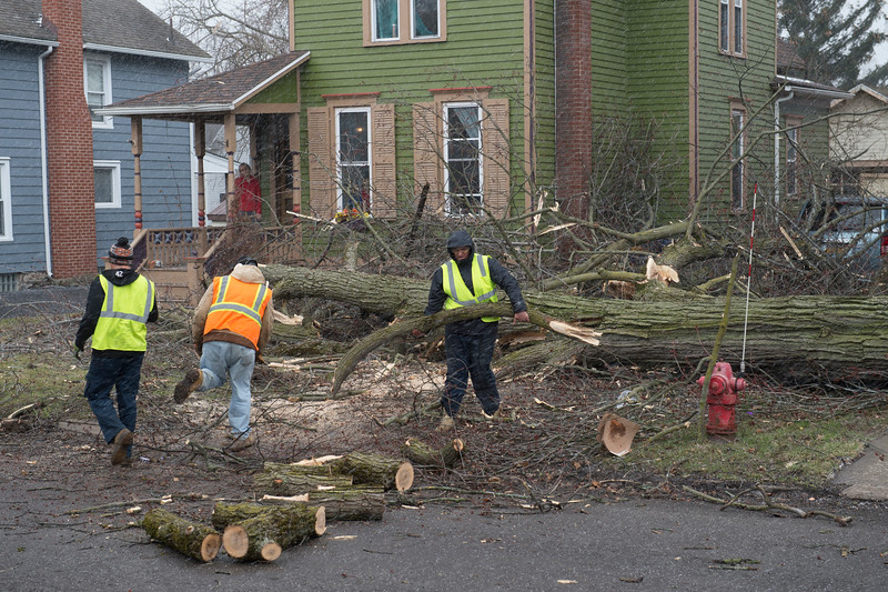 JOED VIERA/STAFF PHOTOGRAPHER- Curious kids watch as city crews pack a chipper with fallen tree limbs on Grand Street Wednesday afternoon. High winds caused a number of fallen trees and power outages across the county.