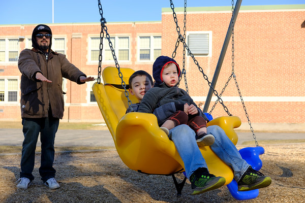 Joed Viera/Staff Photographer-James Kenneth pushes his nephews Shane, 8, and Roland Russell, 1, on the swing set outside of Newfane Middle School Monday afternoon.