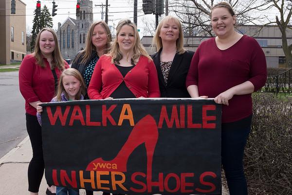 Pamela McKinney, Mae Sadler, Jessica Sandler, Lauren Weihand, Amanda Irons-Rindfleisch and Rachel Sandle-Sacco hold up the YWCA's Walk a Mile in Her Shoes sign.
