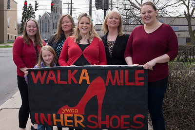 Pamela McKinney, Mae Sadler, Jessica Sandler, Lauren Weihand, Amanda Irons-Rindfleisch and Rachel Sandle-Sacco hold up the YWCA's Walk a Mile in Her Shoes sign.