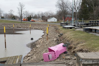 JOED VIERA/STAFF PHOTOGRAPHER-A garbage bin heads into the Canal while NYSEG crews fix a powerline on Market Street Wednesday afternoon. High winds caused a number of fallen trees and power outages across the county.