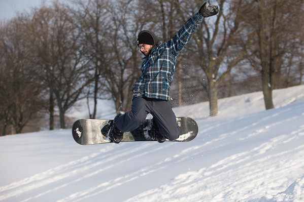 Joed Viera/Staff Photographer-Vincent Lombardo catches some air while snowboarding on a hill at the Lockport Town & Country Club.