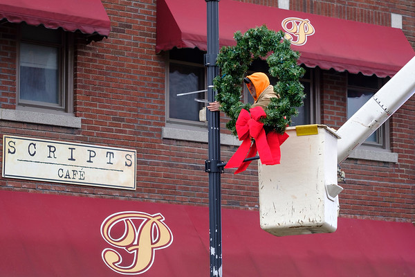 Joed Viera/Staff Photographer-Monday and Tuesday Lockport City workers installed wreaths on fixtures along Main Street in preparation for the holidays.