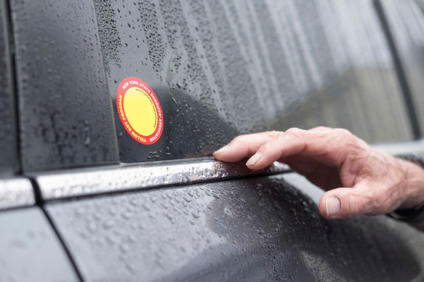 JOED VIERA/STAFF PHOTOGRAPHER-Lockport, NY-George McKinney checks out a yellow dot on a car outside of the Dale Association. The Yellow Dot program is devised to inform emergency personnel of a driver's and passengers' vital health information in event of emergency on road. Participants place a yellow sticker on their vehicles so if they are pulled over, law enforcment instantly know where to look for information.  Kits were  distributed through a partnership with the Niagara County Sheriffs Office. To participate in the program contact assemblyman Mike Norris' office at 716-839-4691.