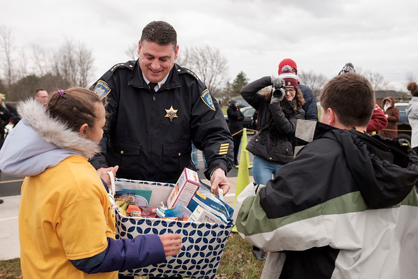 Joed Viera/Staff Photographer- Stairpoint students Kara Walek and Vincent Viele present Niagara County Sheriff James Voutour with a basket of snacks meant for deputies working on the Thanksgiving Holiday during a Lockport Blue Event after the Turkey Trot outside of Douglas J. Regan Intermediate School.