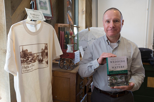 "Joed Viera/Staff Photographer-Ray Wigle holds up a copy of ""Wedding the Waters"" a book about the creation of the Canal and its impacts in the Niagara History Center at 215 Niagara Street. Wigle says he recommends the book to anyone interested in learning more about the Canal."