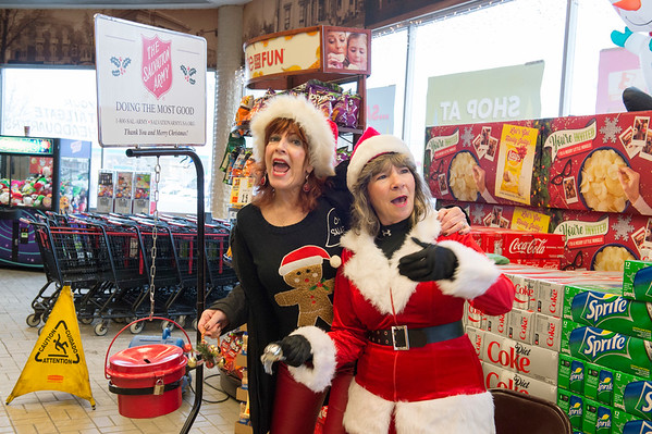 Joed Viera/Staff Photographer- Frankie Waldriff and Jackie Pomeroy sing Christmas carols to attract donors to the Salvation Army's kettle at Tops on South Transit Road.