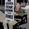 "File photo-Local storyteller and musician Robert ""Goose"" Gray holds a sign protesting a fence that blocks access to a Locust Street parking lot owned by David Ulrich in October 2014"