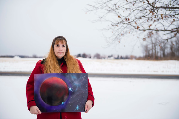 Joed Viera/Staff Photographer- Jennifer Perski holds up one of her late son's pieces of art. Perski's son Daniel, took his own life in March and Jennifer is holding a Stand Against Suicide vigil at the Newfane Town Gazebo on Sunday to raise awareness on the issue.