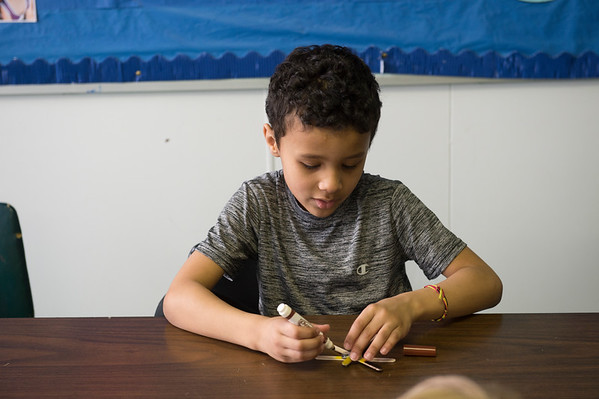 JOED VIERA/STAFF PHOTOGRAPHER-Cayden O'Quinn, 6, paints a popcicle stick dragonfly in the arts and crafts class during the YMCA's Easter Break Day Camp.