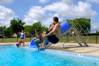 JOED VIERA/STAFF PHOTOGRAPHER-Lockport, NY- Kashawn McTyere 11 and his uncle Josh Davis jump into the Lockport Community Pool.