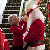 Joed Viera/Staff Photographer- Mrs Clauss watches as Jane Corser adjusts Santa Clauss' cap at the Kenan House. The Clauss' will be at the Kenan Center's annual Holiday Gift Show that takes place this weekend.