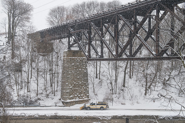 Joed Viera/Staff Photographer-A plow truck clears snow off of the Canal Trail under the Upside Down Bridge.