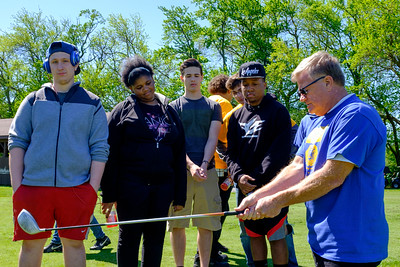 JOED VIERA/STAFF PHOTOGRAPHER-Lockport, NY-Doug Whelan, right, shows Niagara Academy students how to hold a club during the Lions Club's Diverse Students Golf Clinic at Willowbrook Golf Course.