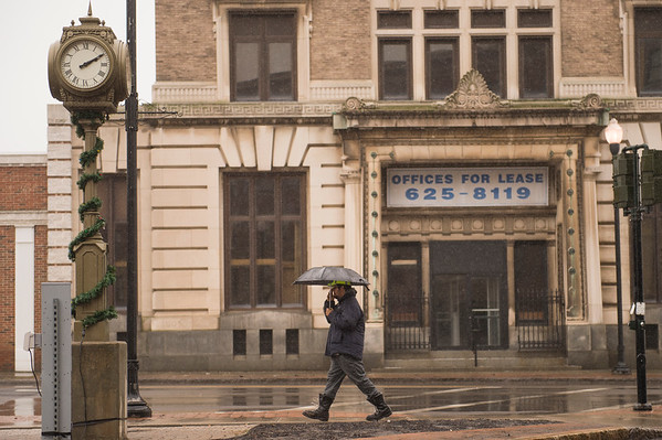 JOED VIERA/STAFF PHOTOGRAPHER-Christopher Boone braves the rain on Main Street while deciding on where to have lunch Thursday afternoon.