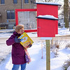 Joed Viera/Staff Photographer-Judy Wolcott stocks the Little Free Pantry behind Emmanual United Church.