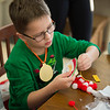 Joed Viera/Staff Photographer- Nathan Hammond, 8, making a Christmas ornament during Starpoint's Winterfest. Winterfest is a yearly tradition where the school's juniors and seniors organize fun holiday activities for kids in kindergarten through fifth grade, this years theme was Grinchmas.