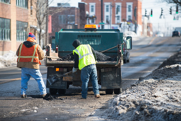 Joed Viera/Staff Photographer-City Workers patch up a section of Walnut Street.