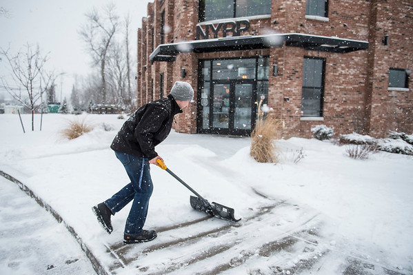 Joed Viera/Staff Photographer-Travis Militello shovels the sidewalks in front of New York Beer Project.