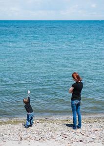 JOED VIERA/STAFF PHOTOGRAPHER-Olcott, NY-Amber Kasperek teaches hers son Jayden 3 to skip stones on Lake Ontario at Olcott Beach.
