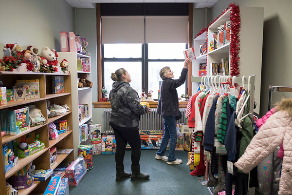 Joed Viera/Staff Photographer-Tiffany and Debbie Barrett shop for at Santa's Sleigh, a make shift toy store for the underprivileged at St John Outreach Center.