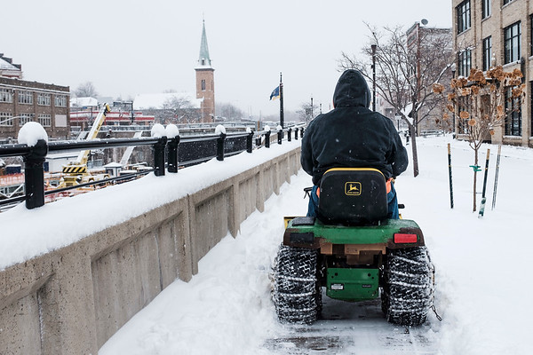 Joed Viera/Staff Photographer-A worker plows the sidewalk on Canal Street with a John Deere tractor.
