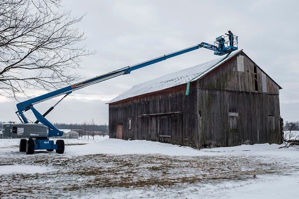 JOED VIERA/STAFF PHOTOGRAPHER-Lockport, NY-A pair of workers install a tarp over the roof of a dilapidated barn on Transit Road.