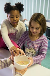 "JOED VIERA/STAFF PHOTOGRAPHER-  Isabella Gibbs, 7, and Lily Caldwell, 8, watch baking soda soaked gummi worms in a glass of vineger ""dance"" in an experiment during the STEM class at the YMCA's Easter Break Day Camp."