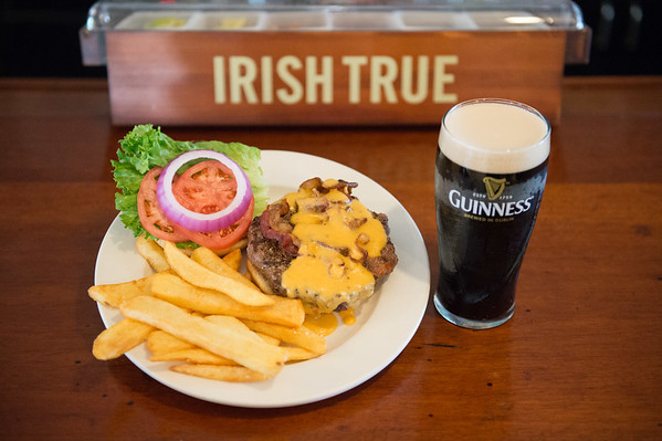 JOED VIERA/STAFF PHOTOGRAPHER- Lockport, NY-The Bacon and Beer Cheese Burger and A Guinness Stout at Ennis' West End Tavern.