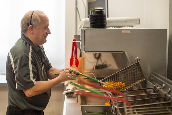 Joed Viera/Staff Photographer-James Graziano makes fries at Arby's on Transit Road. Graziano has been a manager at the sandwich shop for 33 years.