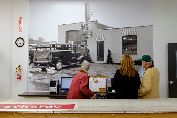 Joed Viera/Staff Photographer-Jane  <br /> Janie and John McCarthy check out a 1954 photograph of Ulrich Sign Co State Street office during the companies open house on Wednesday.