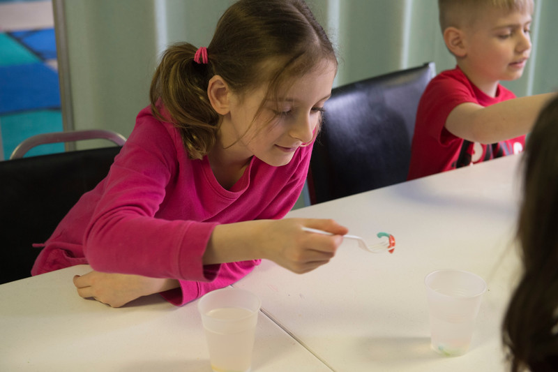 JOED VIERA/STAFF PHOTOGRAPHER- Maria Baldassare, 7, and  Sean Cotrange, 7, place baking soda soaked gummi worms into a glass of vineger for an experiment in the STEM class during the YMCA's Easter Break Day Camp.