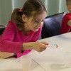 JOED VIERA/STAFF PHOTOGRAPHER- Maria Baldassare, 7, and <br /> Sean Cotrange, 7, place baking soda soaked gummi worms into a glass of vineger for an experiment in the STEM class during the YMCA's Easter Break Day Camp.