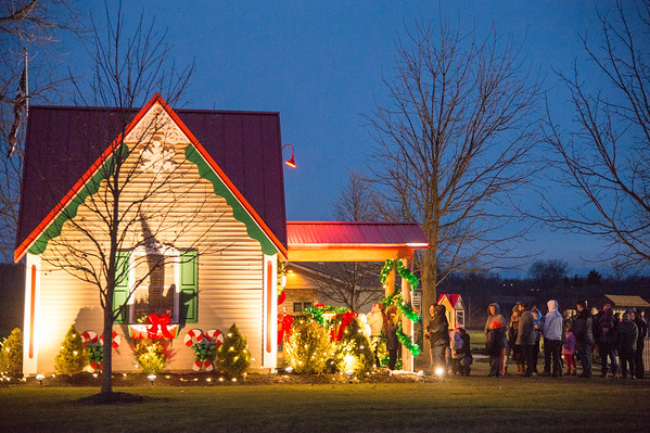 Joed Viera/Staff Photographer-A line forms at Santa Claus' Christmas Cottage in Day Road Park Thursday evening.