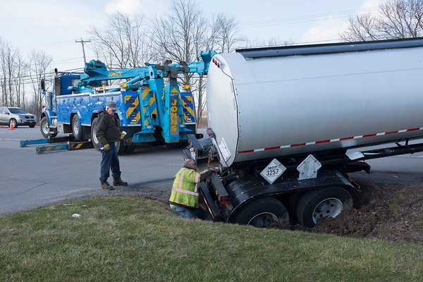 JOED VIERA/STAFF PHOTOGRAPHER-A heavy rig is brought in to lift a tractor trailer filled with hot tar out of a ditch on Transit Road Monday morning. Rapids and South Lockport Fire Companies were on scene diverting traffic.