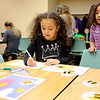 JOED VIERA/STAFF PHOTOGRAPHER- Natalia Baez, 8, looks over her sister Priscilla, 6, as she plays a rhyming game during Books, Balls & Blocks, an literacy outreach program funded by the United Way of Greater Niagara. At the event kids were treated to snacks and games before leavign with copies of bi-lingual books.