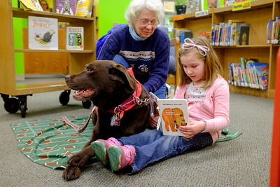 JOED VIERA/STAFF PHOTOGRAPHER-Anne VanDusen looks on as Sophia Kimmel, 5, reads  a book to Abby, the Lockport Public Library's reading therapy dog. Kimmel chose to read Abby her personal copy of  'Brown Bear, Brown Bear, What Do You See?'.