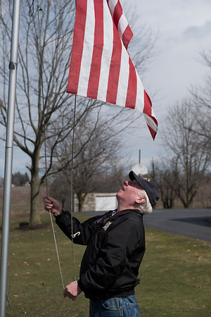 JOED VIERA/STAFF PHOTOGRAPHER-Jack Walsh pulls Old Glory up a flag pole in front of his Chestnut Ridge Road home Thursday afternoon. Walsh doesn't usually take the flag down but Wednesday's high winds left him no choice.