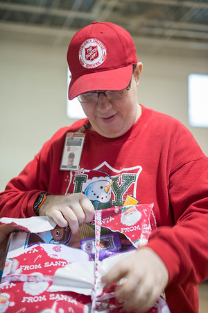 Joed Viera/Staff Photographer-Matt Bowen helps unwrap leftover Christmas donations at the Salvation Army. The organization distrbuted hundreds of donated toys to families Friday. The leftover gifts will be used for next year's campain.