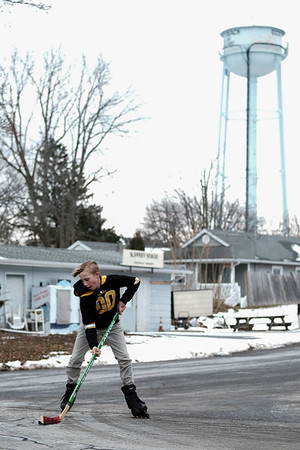 Joed Viera/Staff Photographer-Dominic Masar, 13, takes advantage of the weather Thursday to sharpen his street hockey skills at Jackson Street in Olcott.