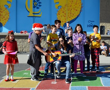2nd grade teacher Yoona Lee leading the school song with members of student council  317