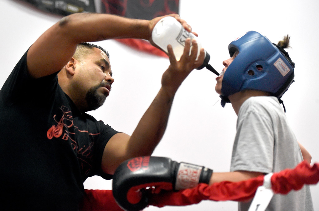 . Owner and trainer Randy Lopez gives water to Shawn Mears, 16, during a sparring match at an after-school boxing class for kids on Thursday at La Familia Boxing inside the YMCA in Longmont. For more photos and video of the after-school boxing program go to www.timescall.com Jeremy Papasso/ Staff Photographer/ May 11, 2017