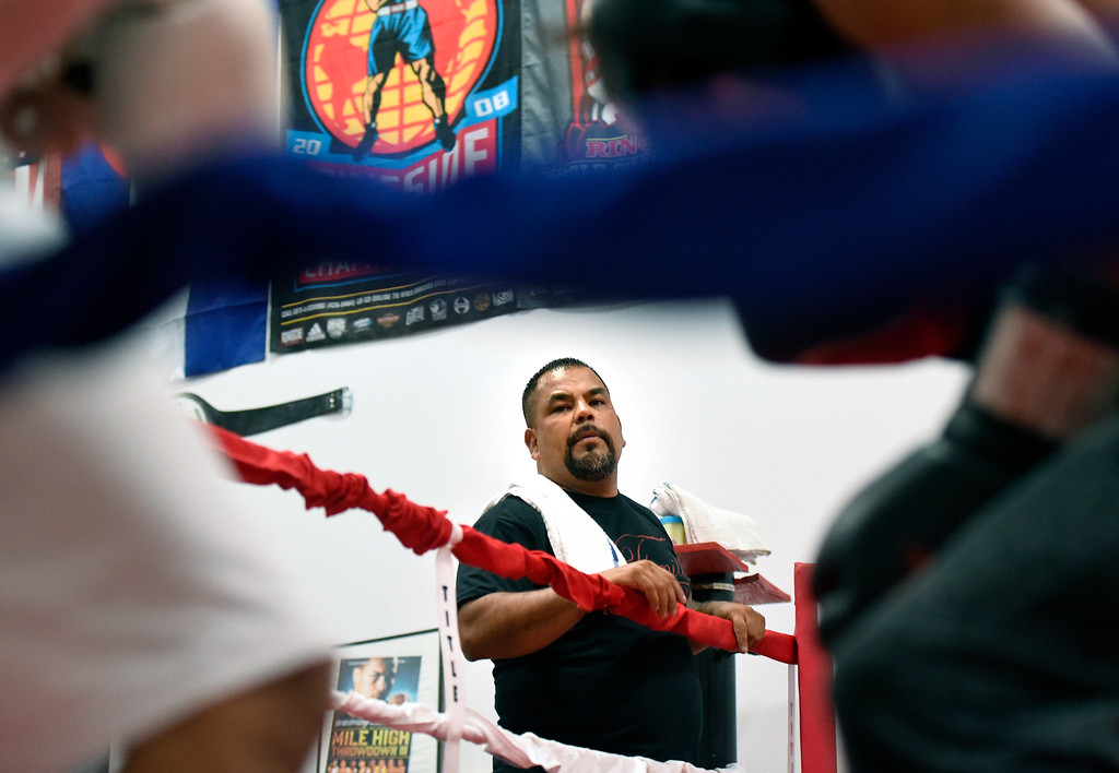 . Owner and trainer Randy Lopez watches as two of  his boxers spar in the ring during an after-school boxing class for kids on Thursday at La Familia Boxing inside the YMCA in Longmont. For more photos and video of the after-school boxing program go to www.timescall.com Jeremy Papasso/ Staff Photographer/ May 11, 2017