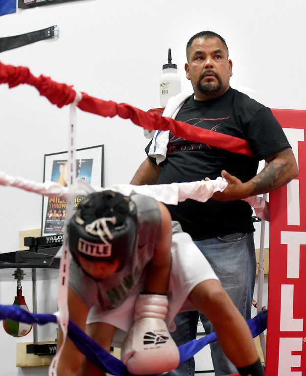 . Owner and trainer Randy Lopez lifts the ropes for a student entering the ring during an after-school boxing class for kids on Thursday at La Familia Boxing inside the YMCA in Longmont. For more photos and video of the after-school boxing program go to www.timescall.com Jeremy Papasso/ Staff Photographer/ May 11, 2017