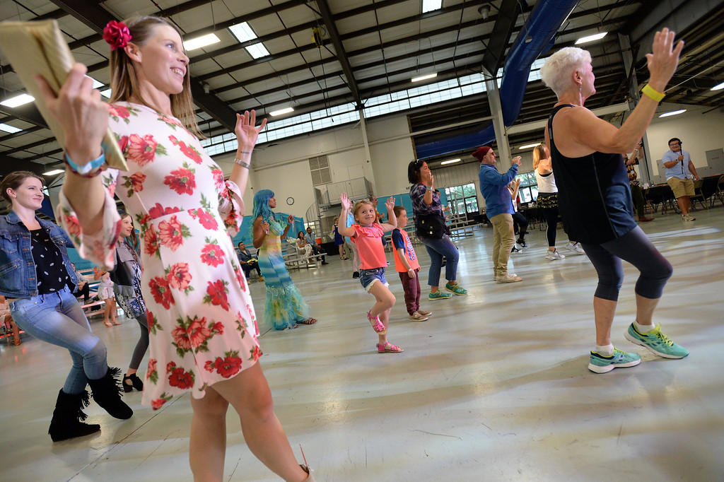 . LONGMONT, CO: September 8: Sara Su-Castillo, left, and her daughter Mila Su, dance to Zumba music  during the La Fiesta Underwater World Party that benefits Intercambio held  at the Boulder County Fairgrounds in Longmont on Saturday. (photo by Cliff Grassmick/Staff Photographer).