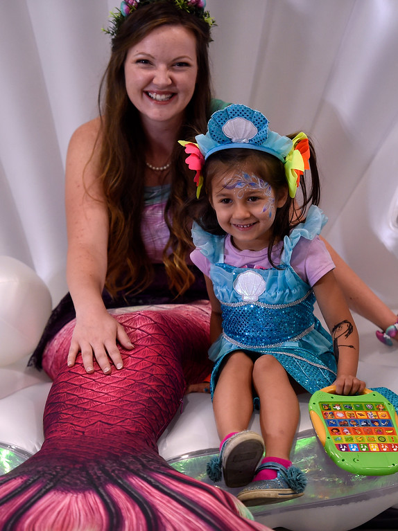 . LONGMONT, CO: September 8:  Delilah Garcia, 4, takes a photo with Trina the Mermaid during the La Fiesta Underwater World Party that benefits Intercambio held  at the Boulder County Fairgrounds in Longmont on Saturday. (photo by Cliff Grassmick/Staff Photographer).