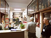 Mike Boitano and John Petito observe the changes that have taken place on the office floor mezzanine since their time at La Salle.  The cubicles are a novelty.  The carved wooden crucifix on the wall with the velvet drapery behind it had been removed long before.  The trophy cases, though, have been in place since before 1953 -- how long before, I don't know.