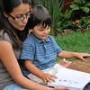 Young Hispanic mother reads to her son