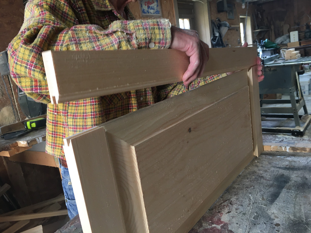 . With enough wooden sections finished, Richard MacKay began to assemble a cabinet front. Photo by Mary Leach